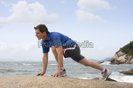 jogger stretches on the beach