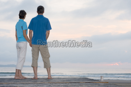 couple on jetty by the sea