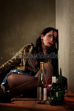 woman surrounded by booze bottles in