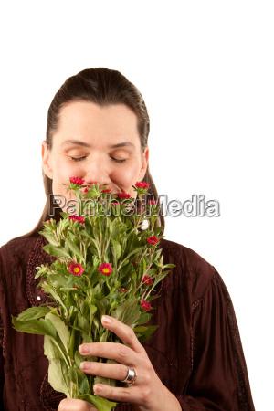 pretty woman smelling flowers