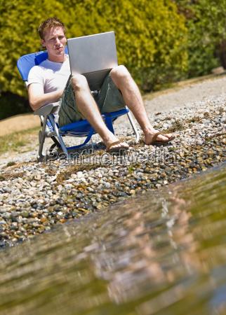 man, using, laptop, near, stream - 2822821