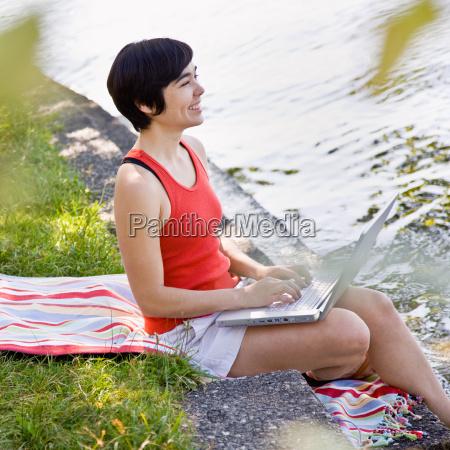 woman, using, laptop, near, pond - 2822777