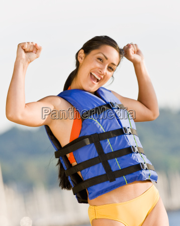 woman wearing life jacket at beach