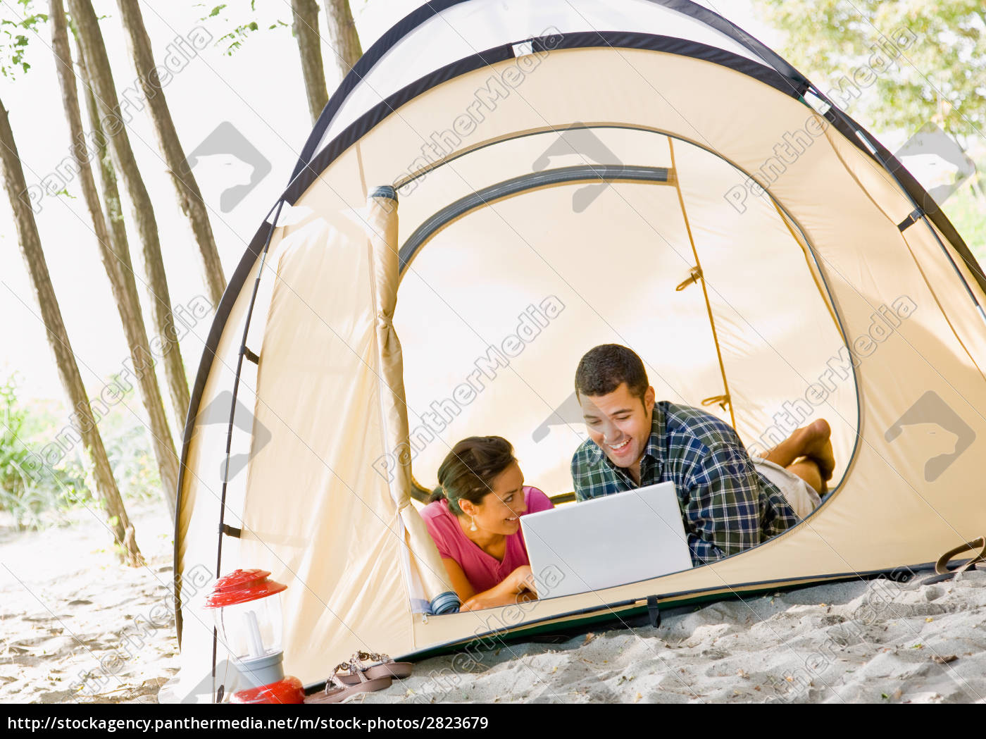 couple, laying, in, tent, using, laptop - 2823679