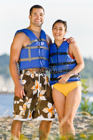 couple, wearing, life, jackets, at, beach - 2823709