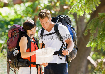 couple, with, backpacks, looking, at, map - 2823011