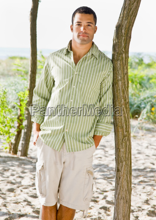 man, leaning, on, tree, at, beach - 2823911