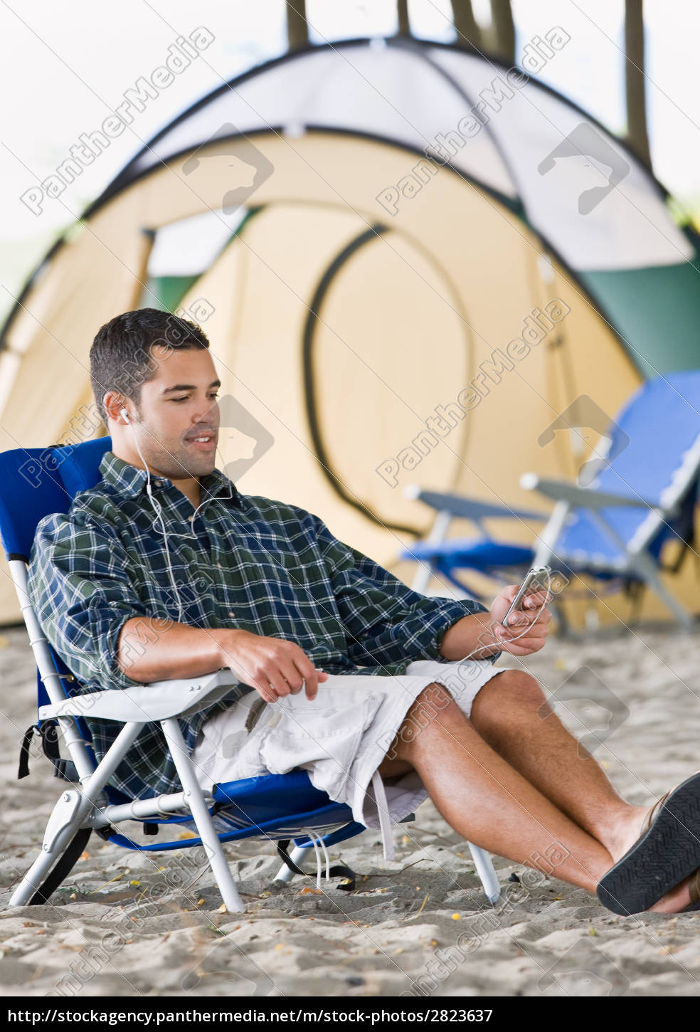 man, using, mp3, player, at, campsite - 2823637