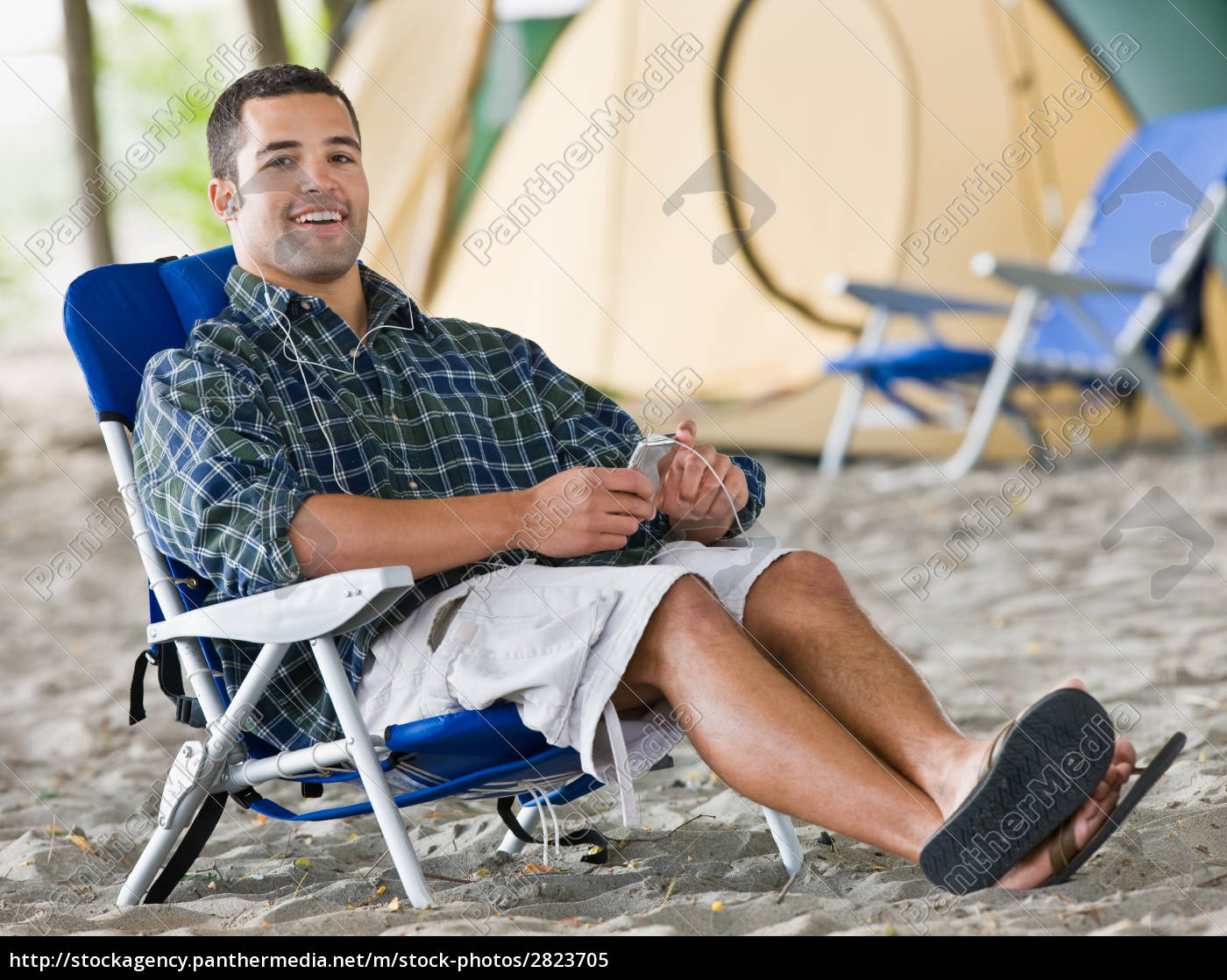 man, using, mp3, player, at, campsite - 2823705