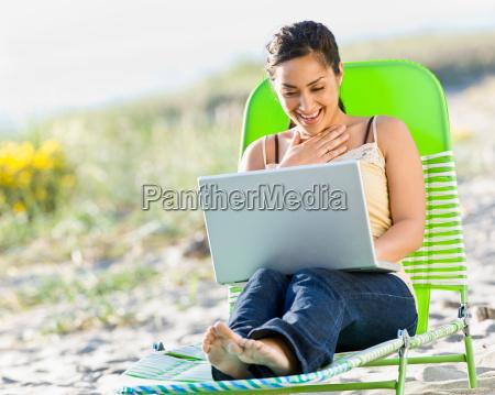 woman, using, laptop, at, beach - 2823609