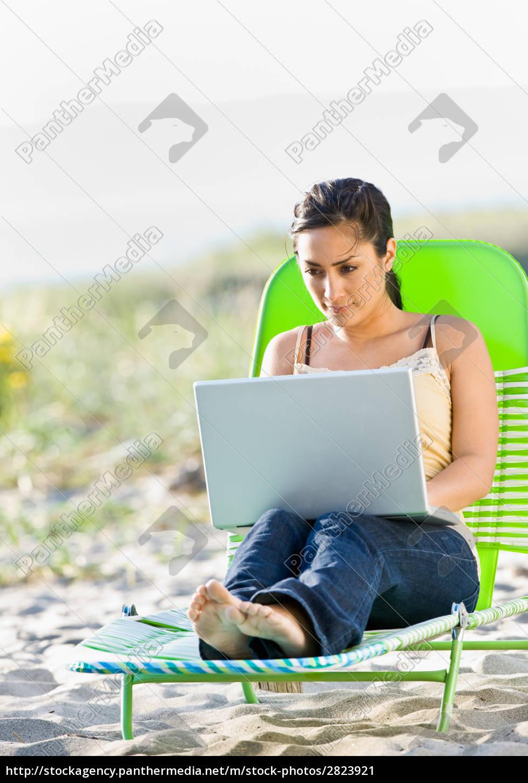 woman, using, laptop, at, beach - 2823921
