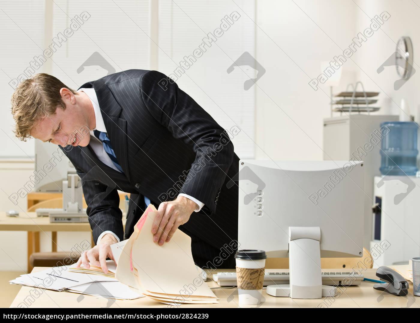 businessman, looking, through, file, folders - 2824239