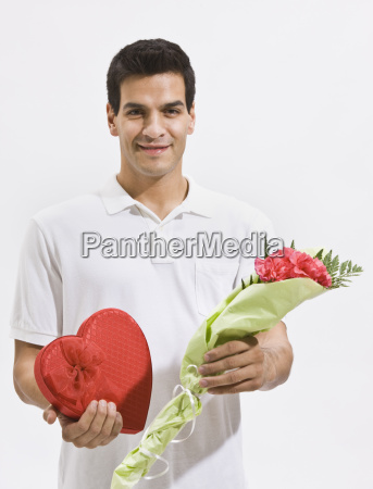 happy man holding candy and flowers
