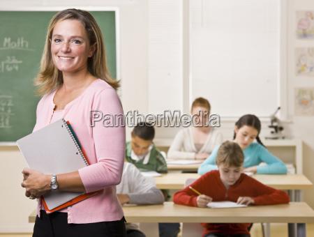 teacher, standing, with, notebook, in, classroom - 2832877