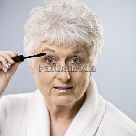 older woman putting on makeup