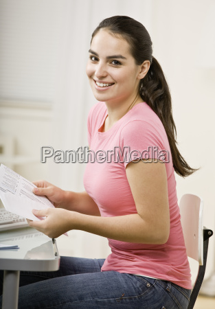 young woman stuffing envelope