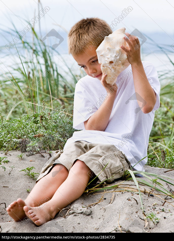boy, listening, to, seashell, at, beach - 2834735