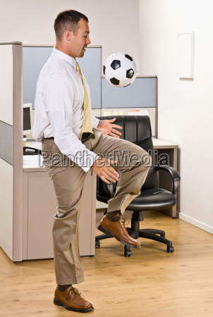 businessman playing with soccer ball in