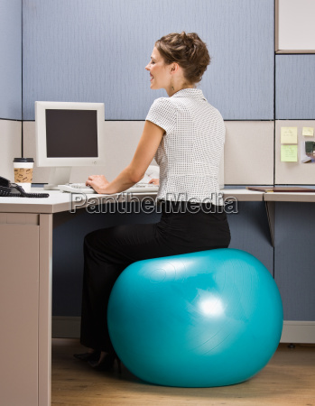 businesswoman sitting on exercise ball at
