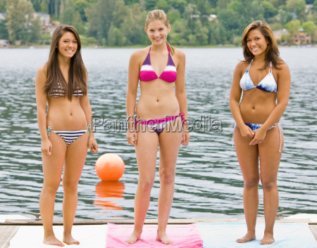 friends in bikinis standing on pier