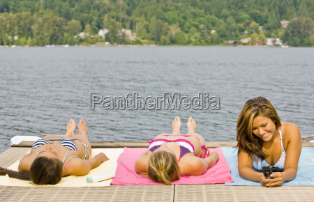 friends laying on pier at lake