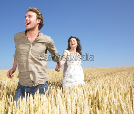 couple running in wheat field