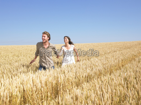 happy young couple in wheat field