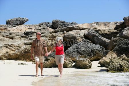 senior couple walking holding hands on
