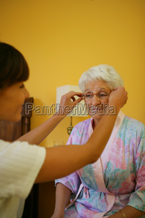 young woman putting eyeglasses to a