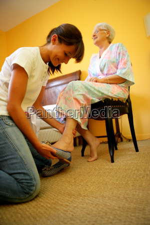 young woman putting chaussons a senior