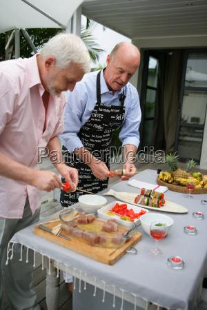 senior, men, preparing, fish, kebabs, terrace - 2937581