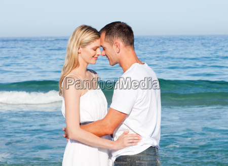 intimate lovers embracing at the beach