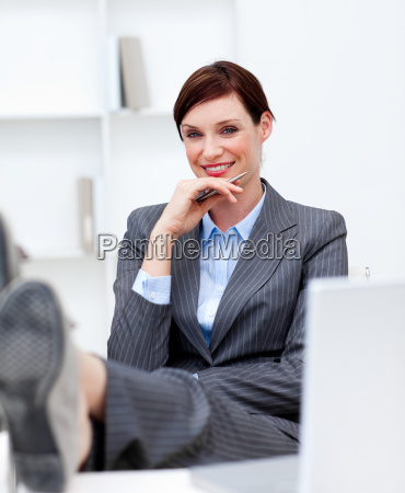 attractive businesswoman leaning feet on desk