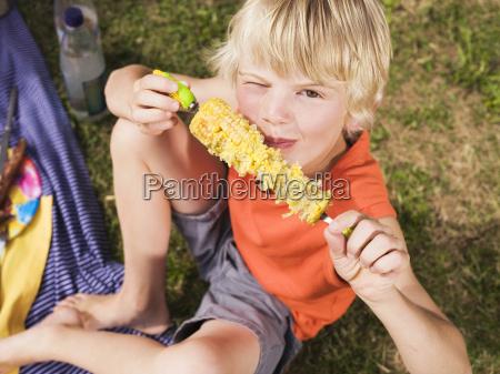boy eating corn cob portrait