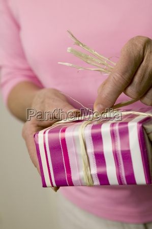 woman holding gift box mid section