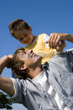 boy sitting on father s shoulders