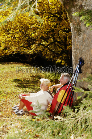senior couple sitting in meadow leaning
