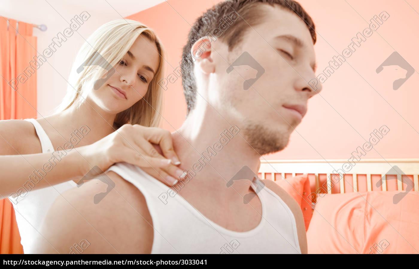 woman, massaging, mans, shoulders, in, bedroom - 3033041