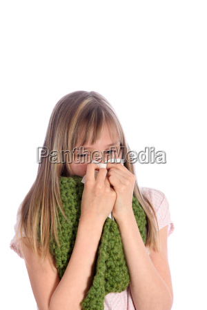 sick young girl blows her nose