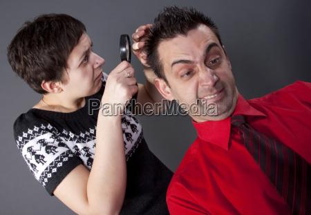 woman examining mans hair