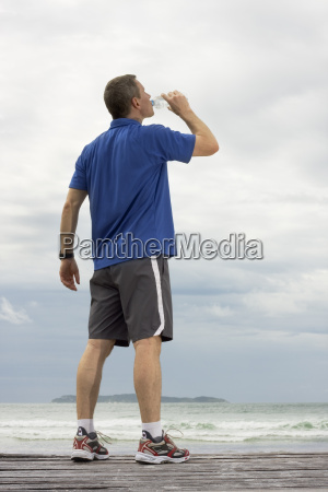 jogger drinking water at the beach