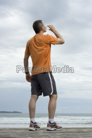 sportsman drinking water at the beach