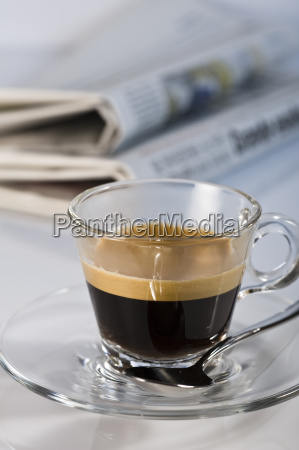 espresso in glass cup with newspaper