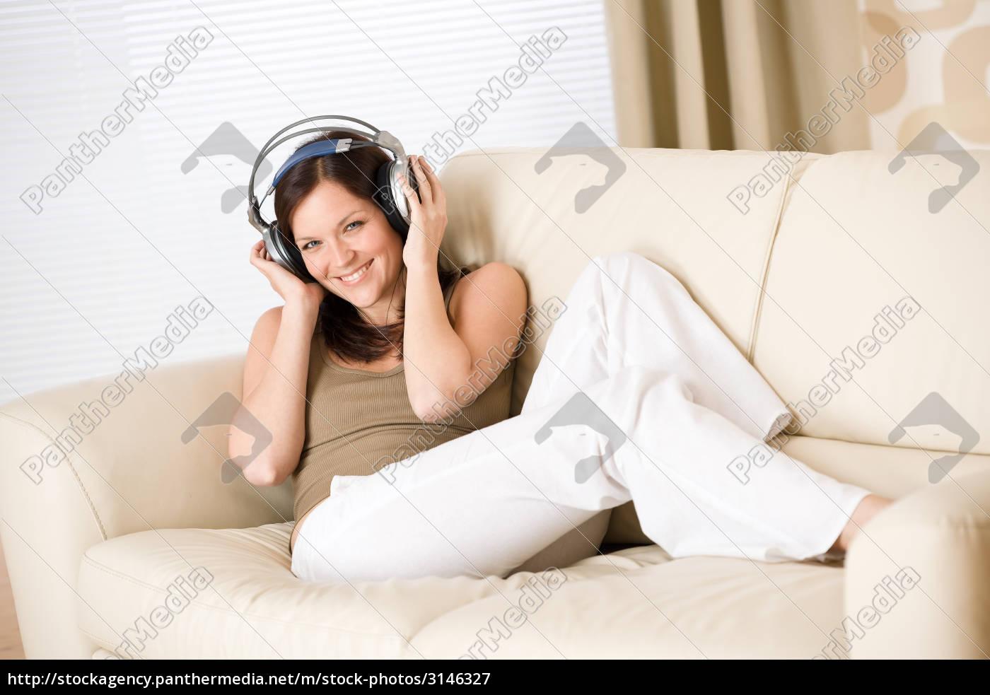 happy, woman, with, headphones, on, sofa - 3146327