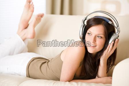 happy, woman, with, headphones, on, sofa - 3146329