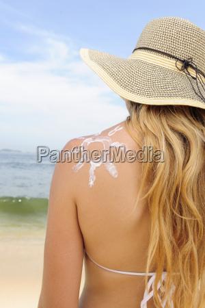woman putting cream on the beach