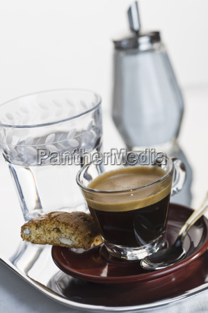 espresso on red plate with cantuccini