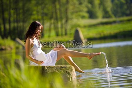 happy romantic woman sitting by lake
