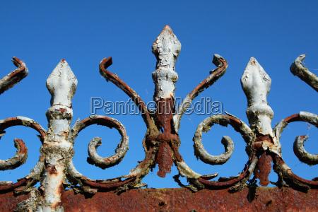 rusty fence against a blue sky