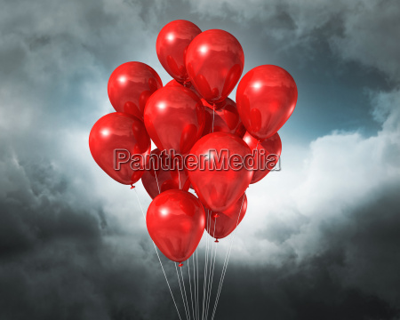 red balloons on a cloudy dramatic
